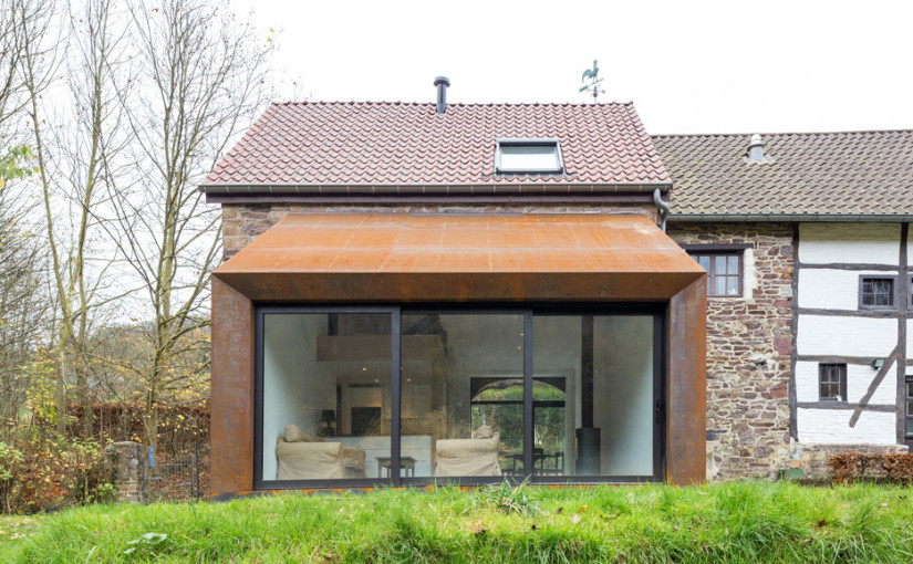 Puzzles Architecture adds rusted steel extension to Belgian barn